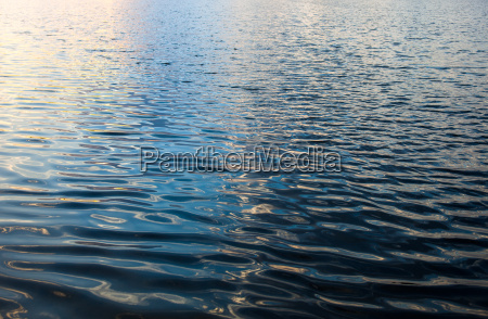 water surface with ripples and sunrays