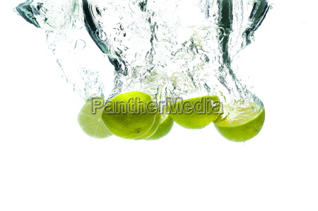 lime fruits fall deeply under water