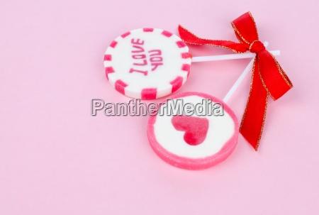 two valentine lollipops on pink background