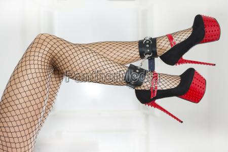 legs wearing fishnet stockings ankle cuffs