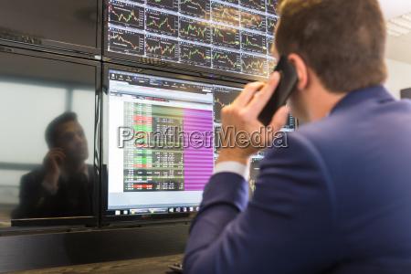 stock trader looking at computer screens