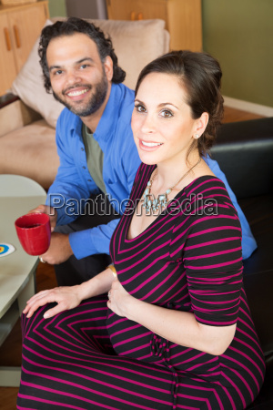 expecting couple holding coffee