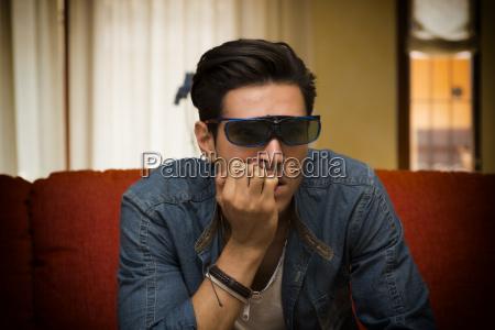 man wearing 3d glasses sitting watching