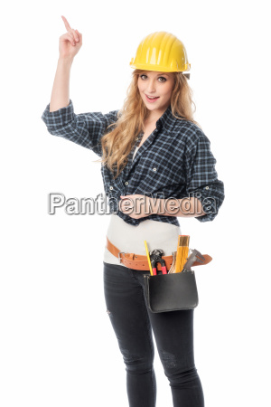 female craftsman with construction helmet pointing