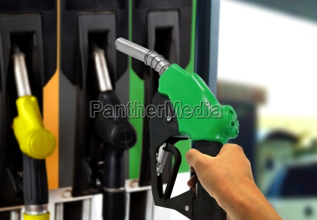 hand holding gas nozzle at gas