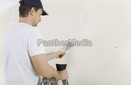 man spackles cracks on wall