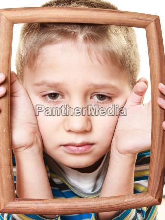 little sad boy child framing his