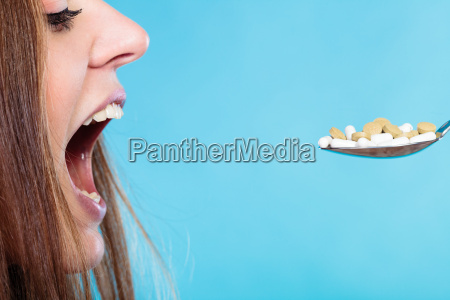 young woman eating pills on a