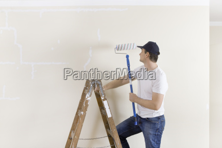 man on ladder with paint roller