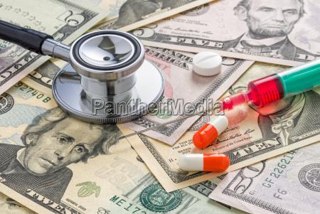 stethoscope and medicines on dollar bills