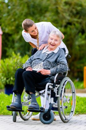 altenpflegerin pushes senior in wheelchair