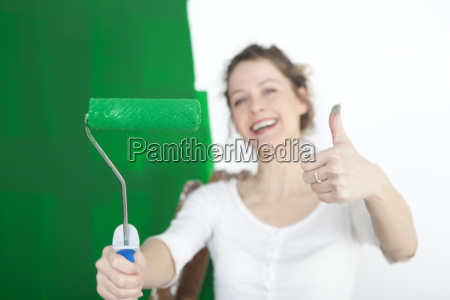 woman with paint roller thumbs up