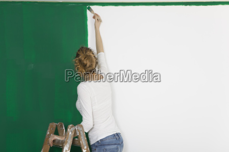 woman with brush before greener wall