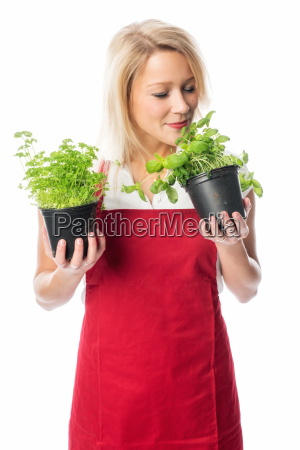 woman with apron smelling a pot