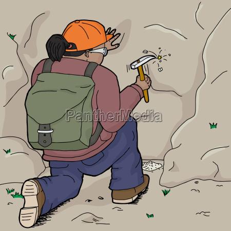 hispanic geologist chiseling samples