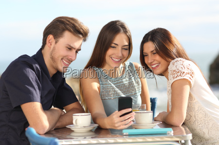 group of friends watching social media