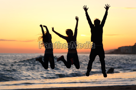 friends silhouette jumping happy on the