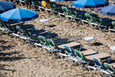 deck chairs over the sand in