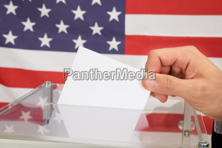 person casting a ballot in front