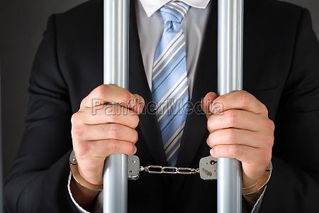 handcuffed businessman holding bars