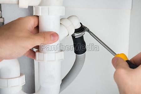 plumber repairing sink in bathroom