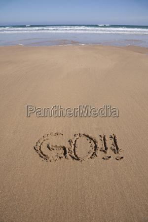 go text in sand beach