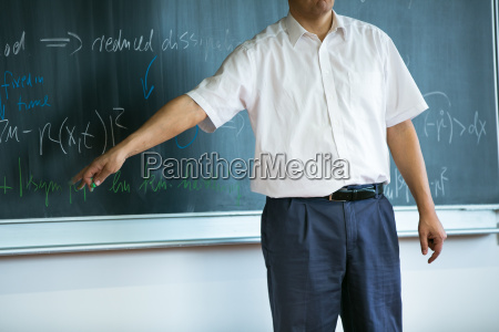 teacher teaching mathematics while pointing at