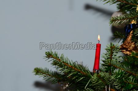 burning candle on christmas tree