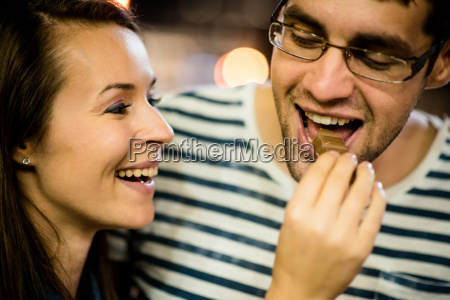 couple eating chocolate on date at