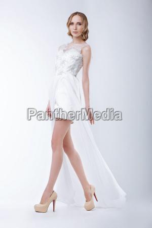 slender fashion model wearing white dress