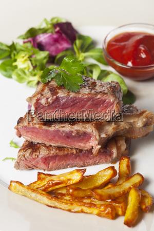 sliced u200bu200bbeef steak with french fries