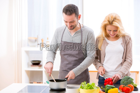 young attractive couple cooking in a