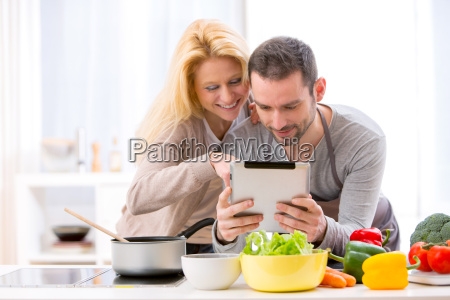 young attractive couple reading recipe on