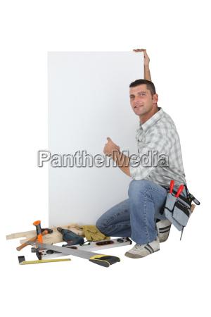 carpenter posing by advertising panel