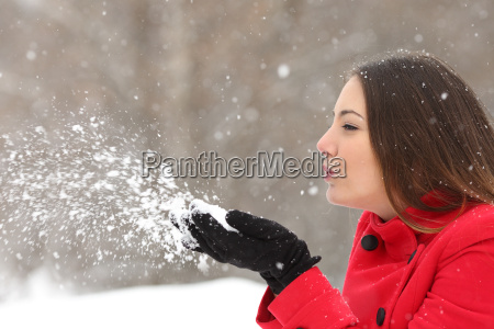candid woman in red blowing snow