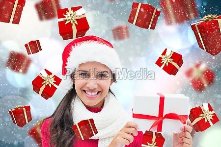 composite image of festive brunette holding