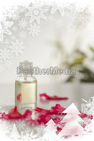 glass phial and pink petals in