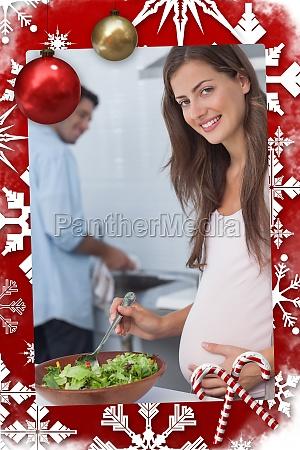 pregnant woman preparing a salad in
