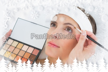hand applying eyeshadow to beautiful woman