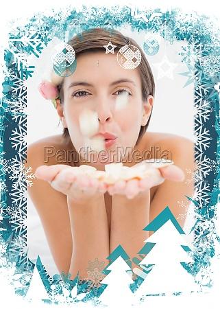 beautiful happy woman blowing flower petals