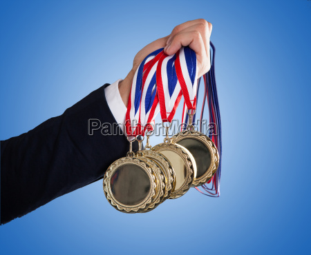businessmans hand holding medals over blue
