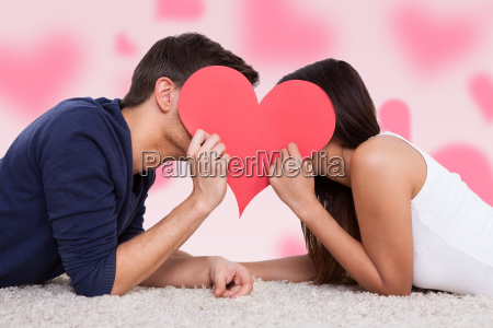 couple kissing behind heart while lying