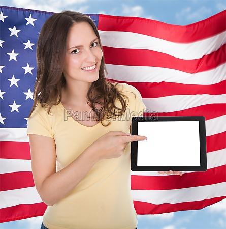 smiling woman holding digital tablet