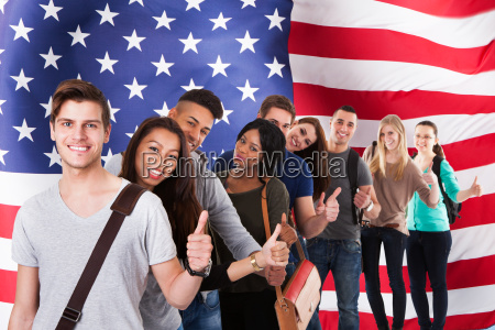 college students gesturing thumbs up in