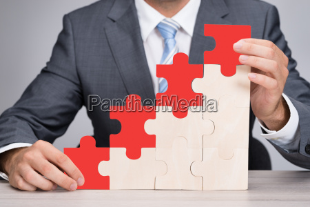 businessman holding red jigsaw graph on