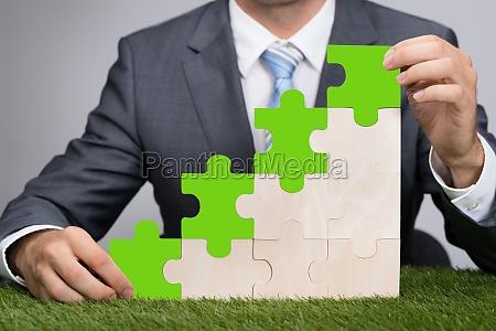 businessman, holding, jigsaw, graph, on, grass - 13687032