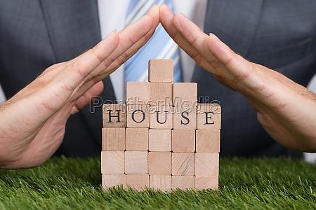 businessman, protecting, house, blocks, on, grass - 13687018