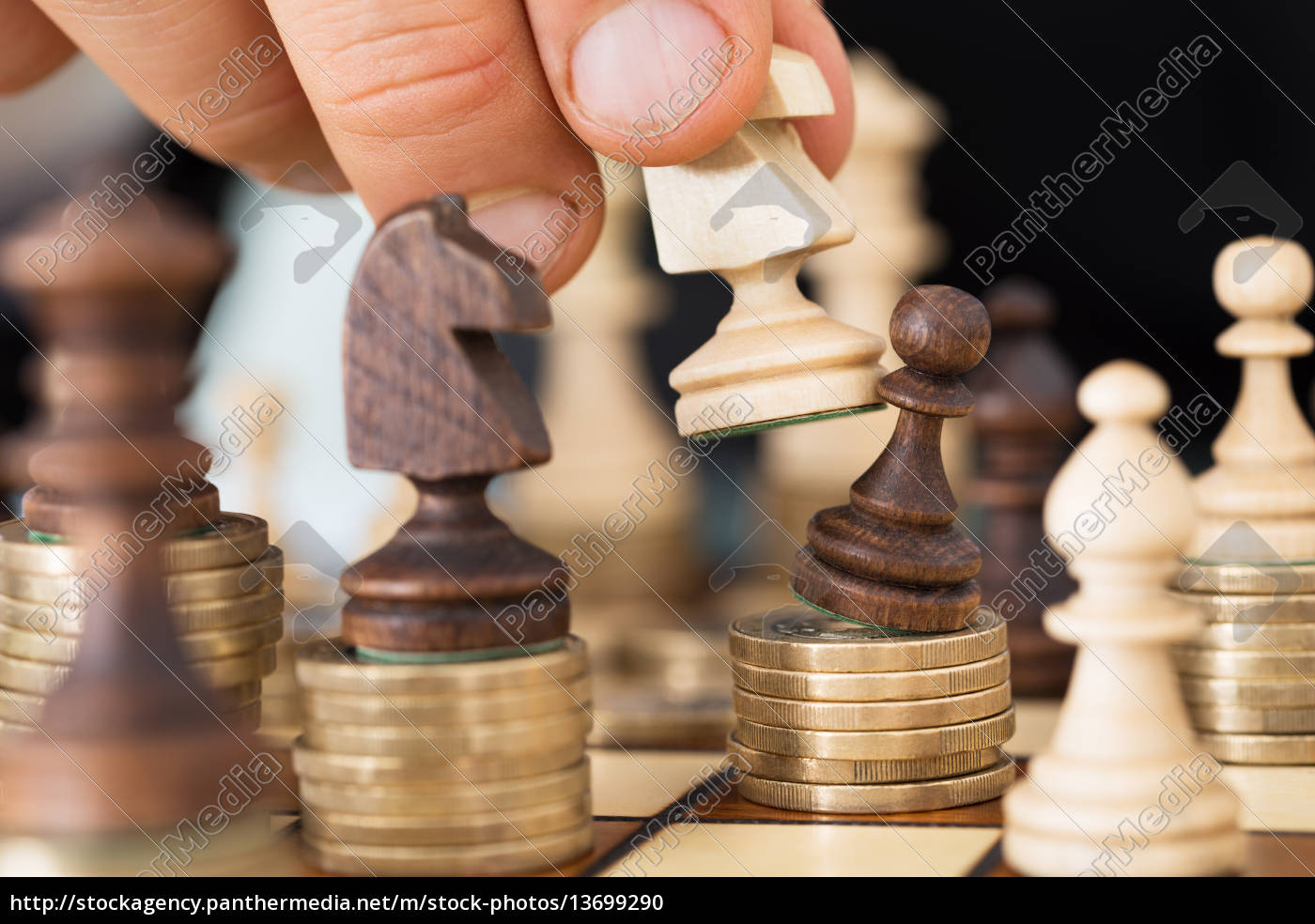 Royalty free image 13699290 - Hand Playing Chess Stacked On Coins