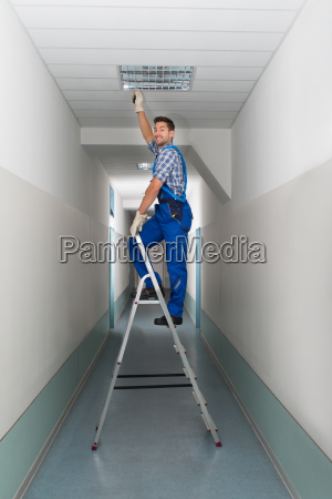 electrician, on, stepladder, installs, lighting, to - 13699344