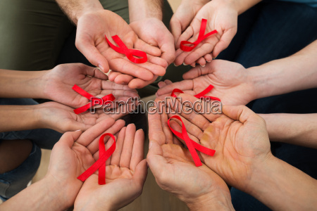 people holding aids ribbon